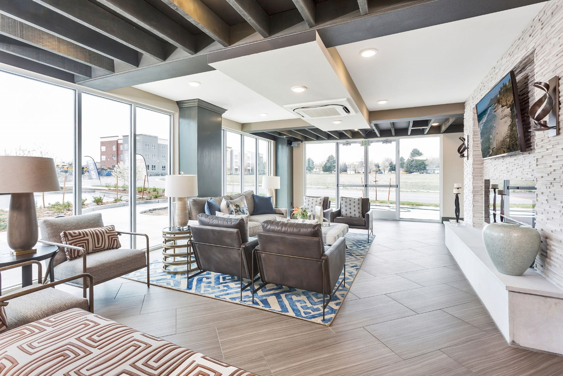 Westwood Green Apartments Clubhouse Lounge with oversized furniture, fireplace, and tv