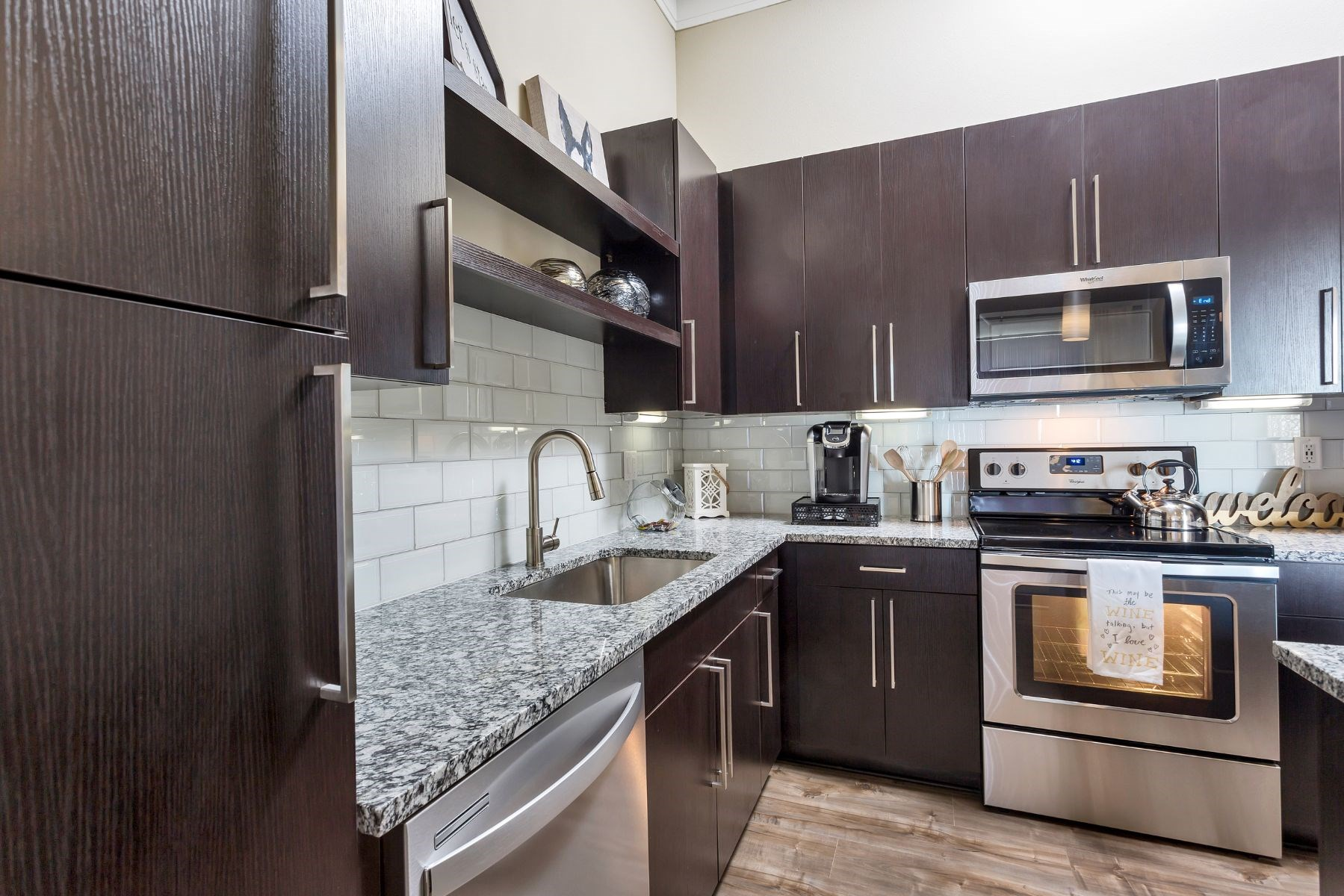 Westwood Green Apartments Kitchen with stainless appliances, grey quarts countertops, and white subway tile backsplash