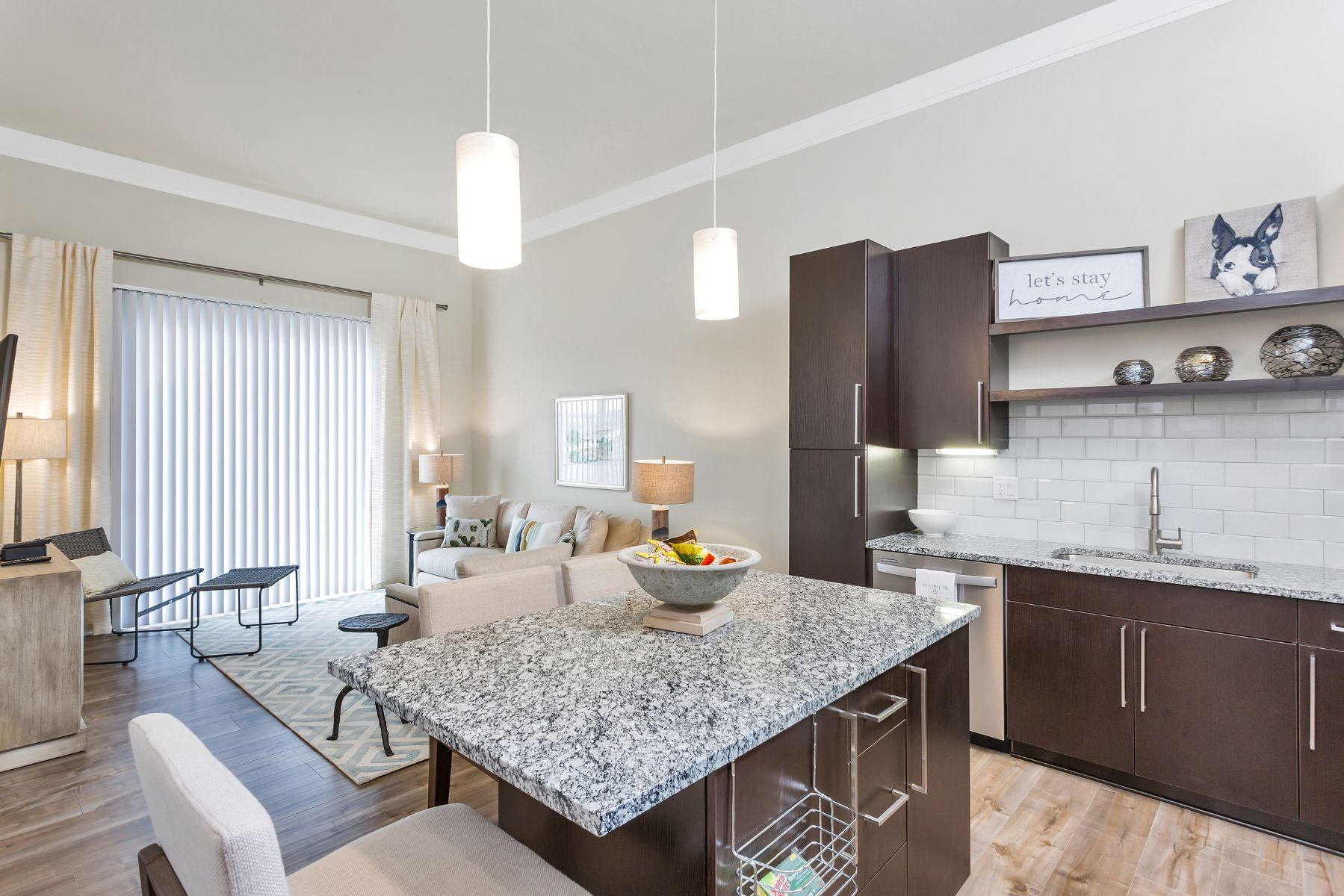 Westwood Green Apartments open floorplan Living Room and Kitchen with large island, stainless appliances, and quartz countertops