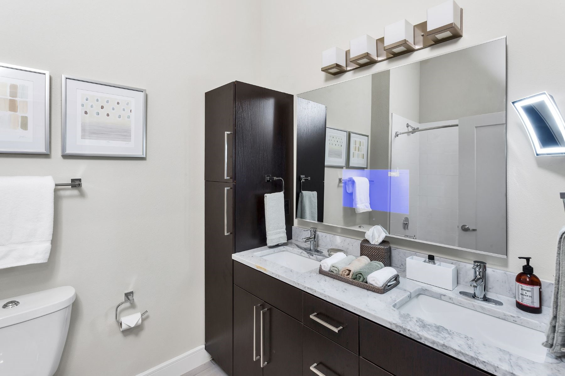 Westwood Green Apartments Bathroom Vanity with embedded tv in mirror and quarts countertop with 2 undermount sinks