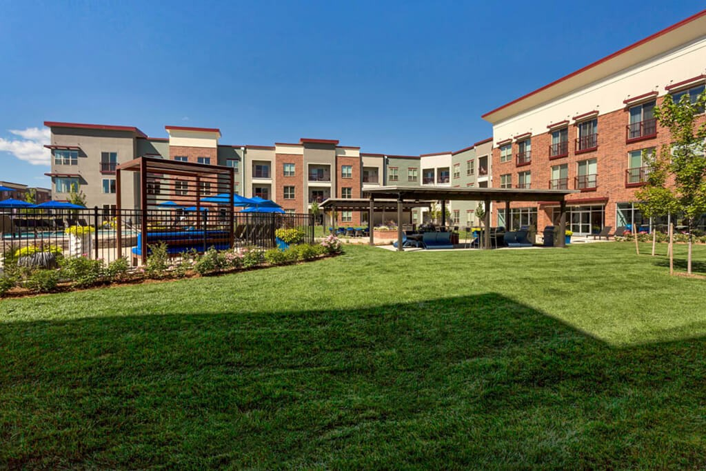 Westlake Greens Courtyard with grass, fenced in pool, pergola, and apartments behind