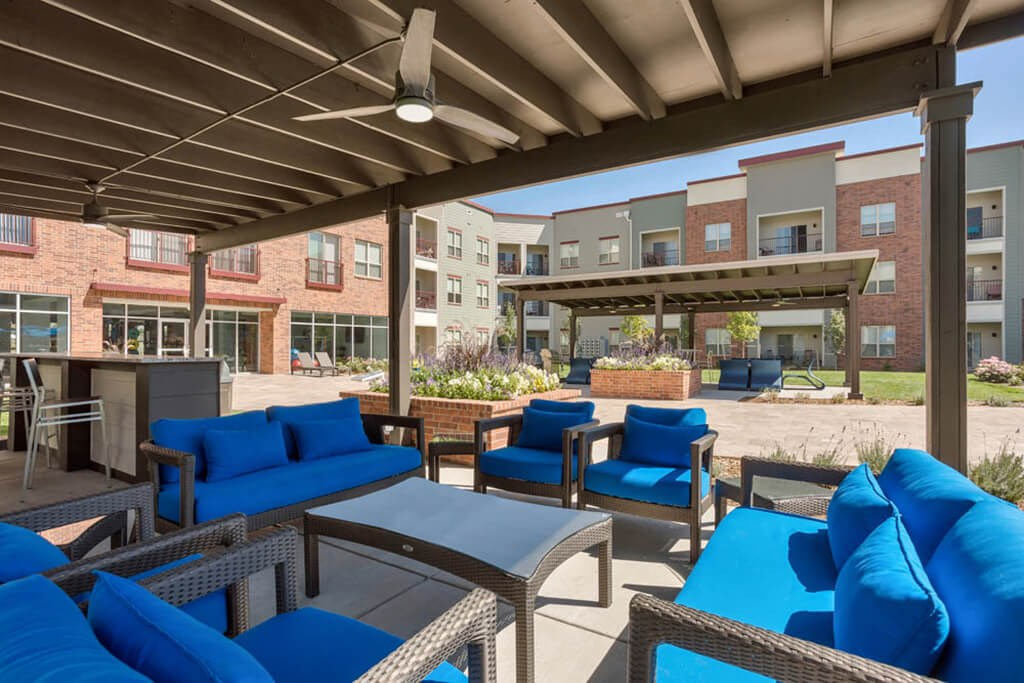 Westlake Greens blue patio furniture with brown metal awning above it