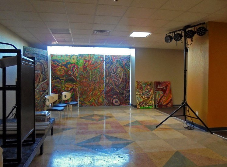 large room with murals, studio lighting and chairs for seating
