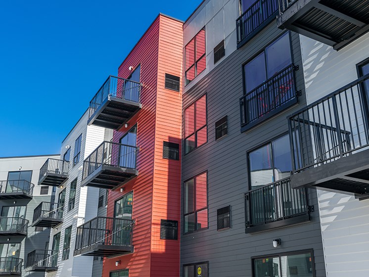 outside of red, gray, and white apartments with balconies