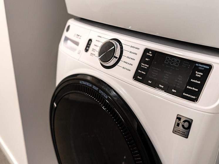 modern, white laundry washing machine with black door and knobs
