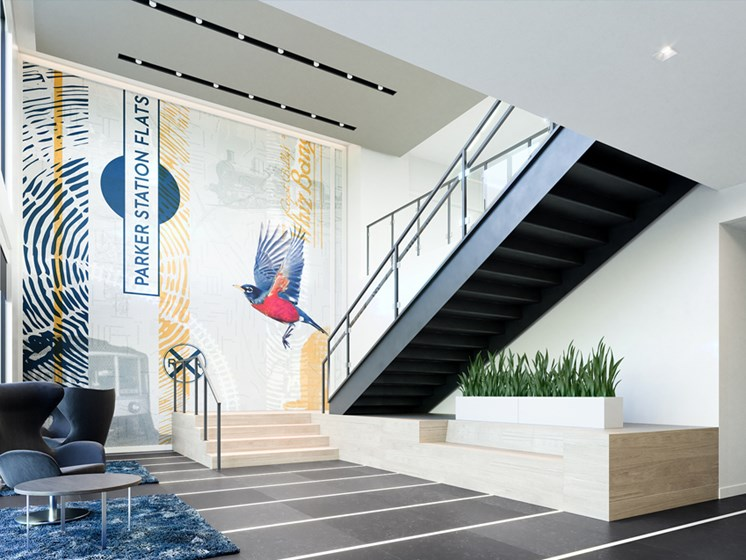 lobby with chairs, potted plants, and stairs against a mural of a bird and a sign that reads