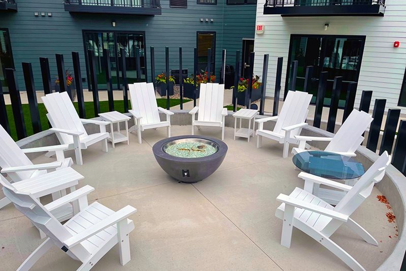 white chairs surrounding a decerative gas firepit