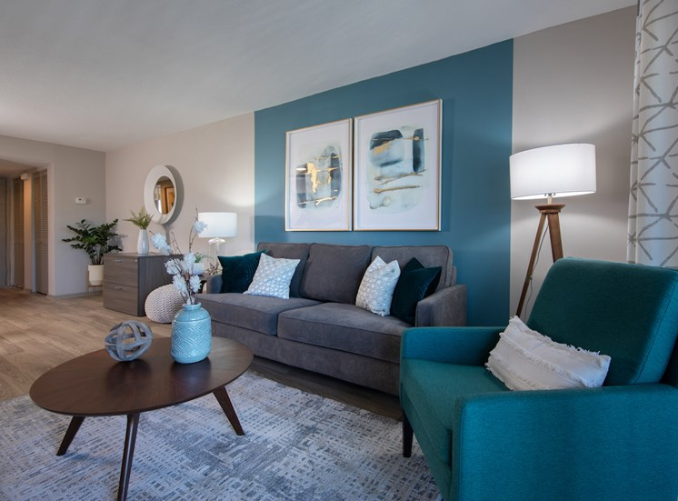 Living room with accent wall, plank flooring, and model furnishings