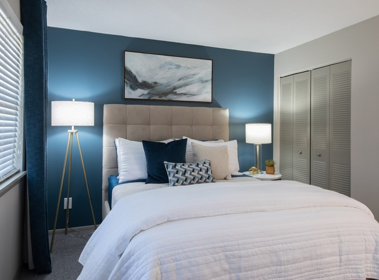 bedroom with accent wall, closet, and model furnishings
