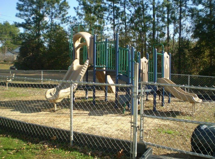 fenced play area with modern playground equipment