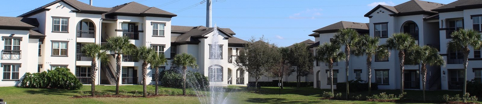 fountain in front of palm trees and apartment buildings