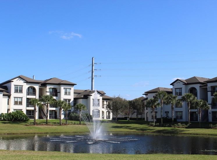 Fountain in pond beside apartment homes at Lake Nona Water Mark