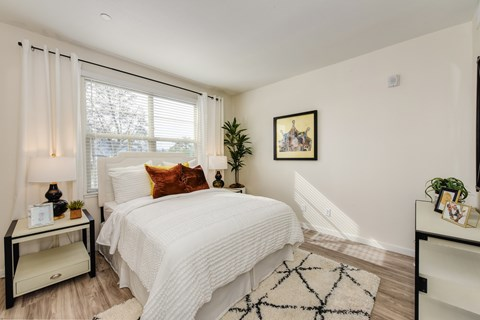 Master bedroom with queen size bed under the large window.  Nightstand table with lamp on the side of the bed.  Faux plant in corner of the room.