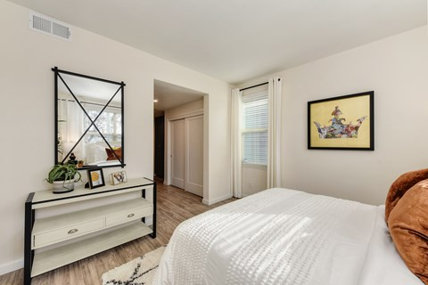 Master bedroom with white bed and copper colored throw pillows, Black and white dresser with mirror positioned above it.