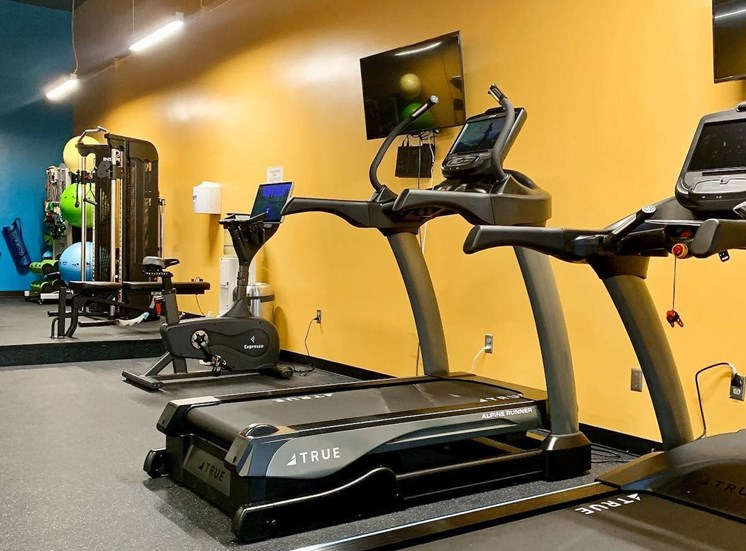 Fitness center with exercise equipment and large mirrors