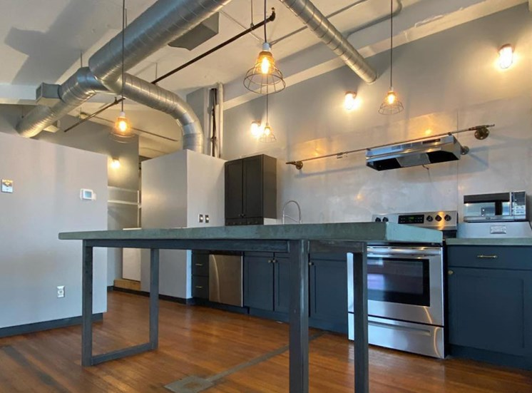 upgraded kitchen with pendant lighting, stainless steel appliances, and concrete island