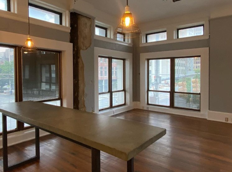 Spacious living area with floor to ceiling windows and hardwood floors