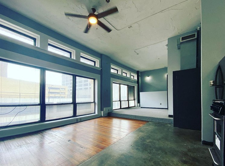 large windows in loft with ceiling fan and hardwood and concrete floors