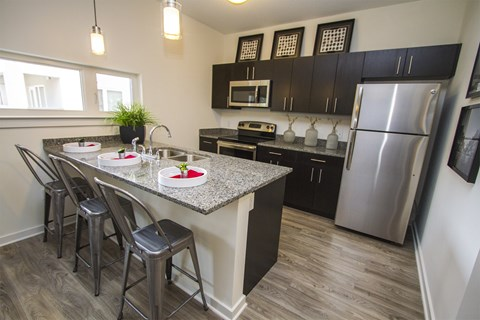 Kitchen with stainless steel appliances, granite countertops, dark wood cabinetry, three person seated bar and hardwood flooring