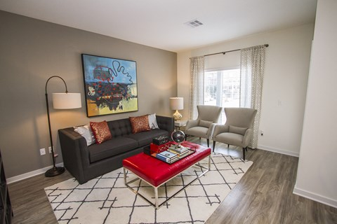 Living room with hardwood floors, couch and two sitting chairs. One large window with drapes