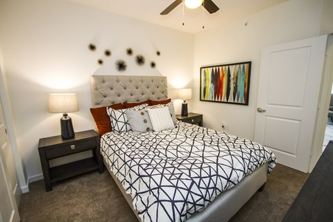 Bedroom with queen size bed and two nightstands, ceiling fan light and carpeted floors
