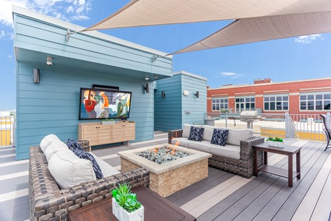 Rooftop patio space with skyline views and firepit