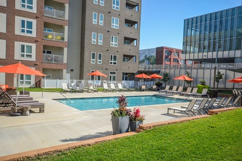 Pool outside of the building that has lounge chairs, grilling station, and umbrellas