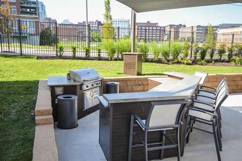 Outside grilling station with gas grill and bar with seats located next to the pool