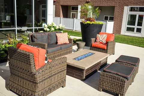 Outside pool furniture consisting of a couch and two chairs with ottomans and a firepit