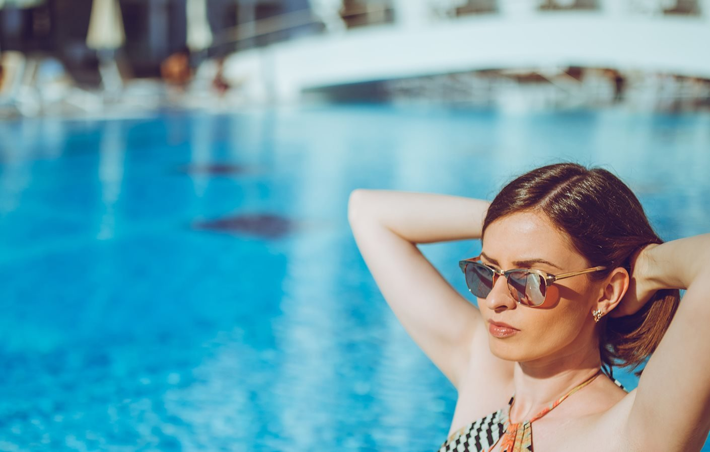 photo of woman relaxing near pool