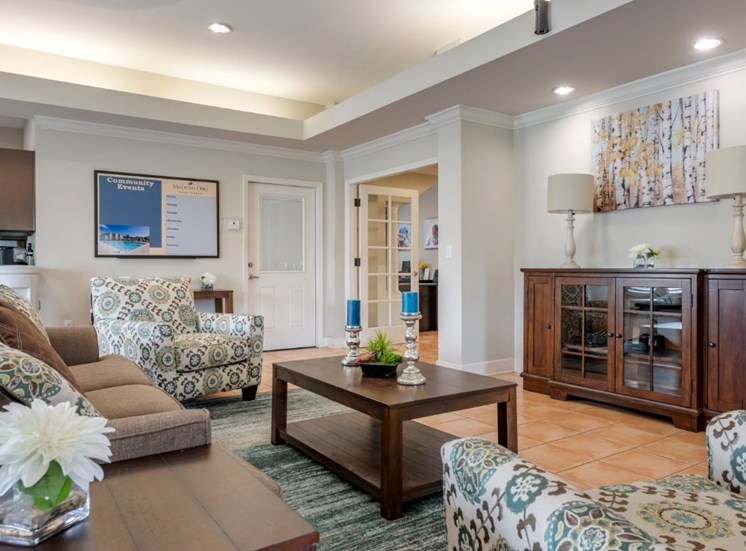 Clubhouse lounge with couch, chairs, coffee table, wall art, tile flooring, and rug
