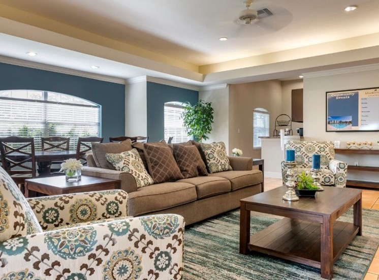 Clubhouse lounge with couch, large dining table, and multi speed ceiling fan chair, coffee table, rug,