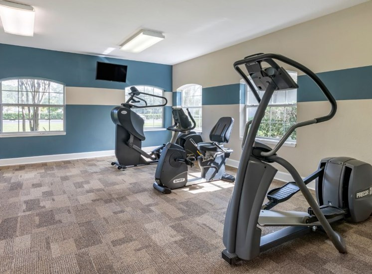 Fitness center with cardio equipment, wall mounted television, and large mirror for natural lighting