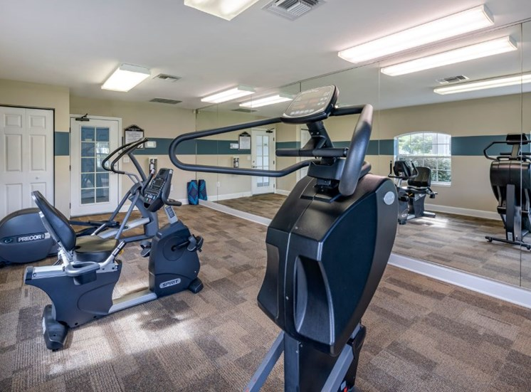 Fitness center with cardio equipment and large mirrors