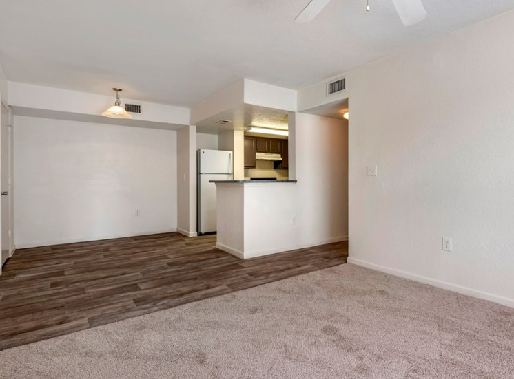 Spacious living room with carpet flooring, dining room with hardwood style flooring, and kitchen breakfast bar