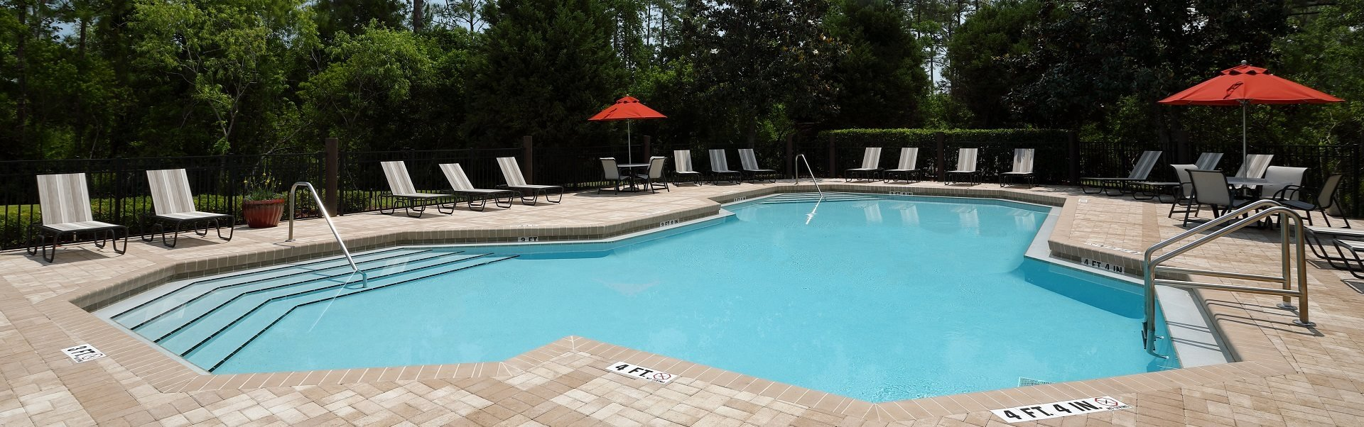 Swimming Pool with Lounge Seating, shaded picnic tables, surrounded by native landscaping