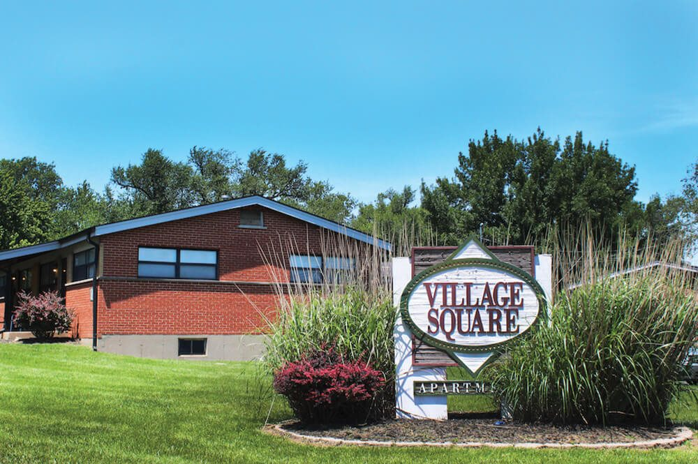 welcome sign at Village Square Apartments