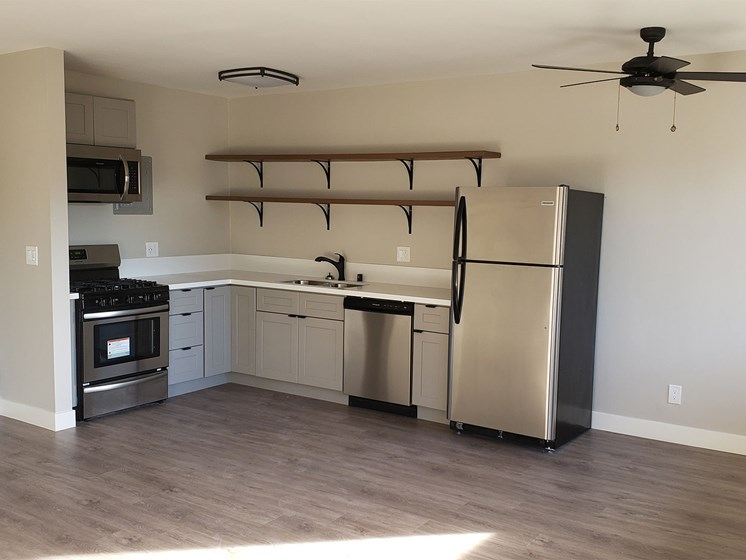 Kitchen Area with Shelf Units, White Countertops, Stainless Steel Appliances, Hardwood Flooring at Wilson Apartments