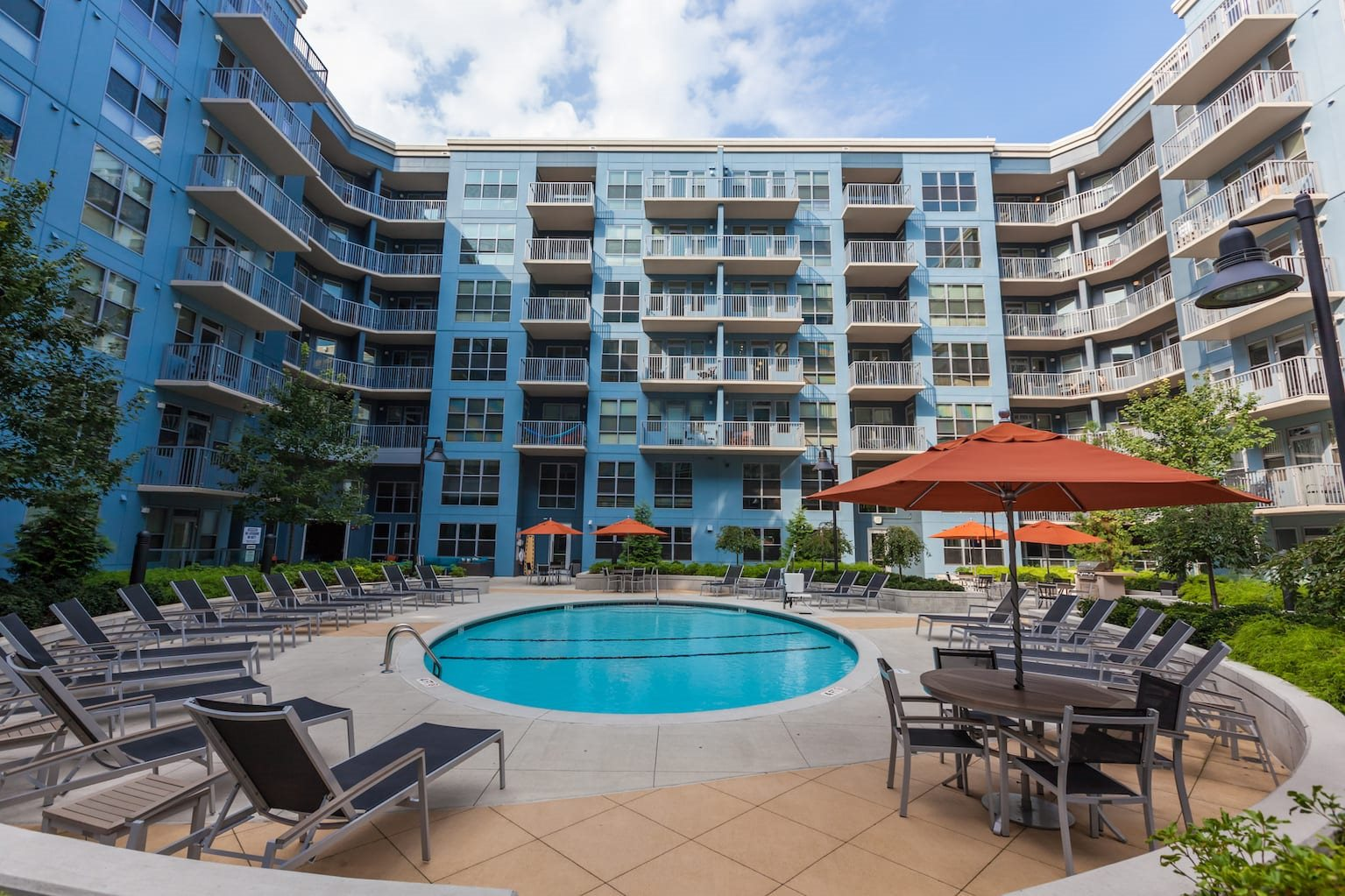 Radius at the Banks Apartments for Rent in Cincinnati, OH Resident Outdoor Pool and Sundeck with Lounge Seating, Firepit, and Grilling Areas