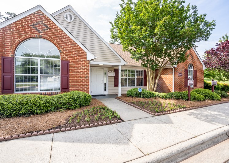 The exterior of the Leasing Office is a brick building with tan siding and burgundy shutters. There is a sidewalk leading to the front door with a large flower bed out front.