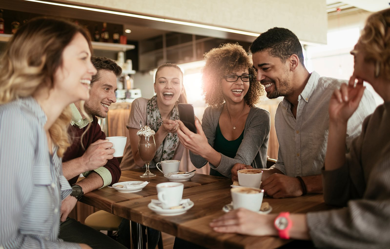 Group of people conversing over coffee