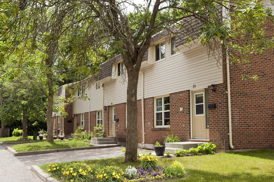 Tamarack Woods Several townhouse exteriors next to each other with neatly clipped green grass and lush trees in Barrie, ON