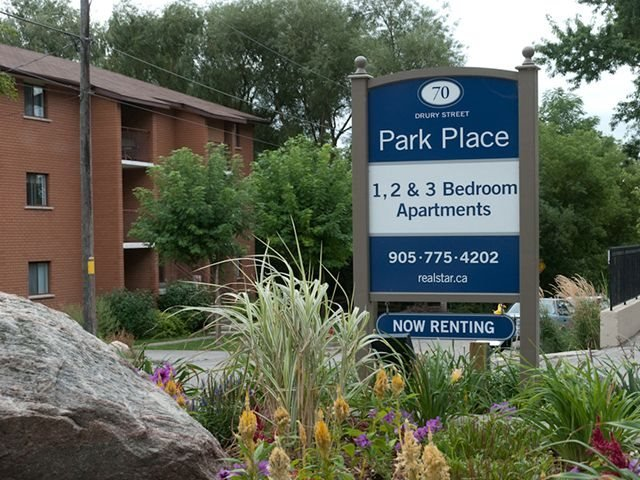 Park Place sign next to beautiful flowers, lush trees and natural rocks.