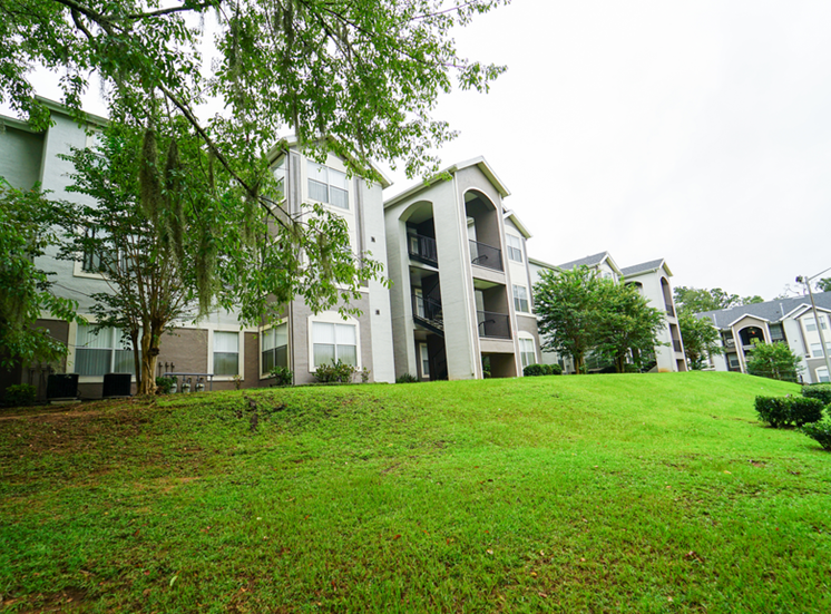 Apartment building exterior surrounded by native landscaping