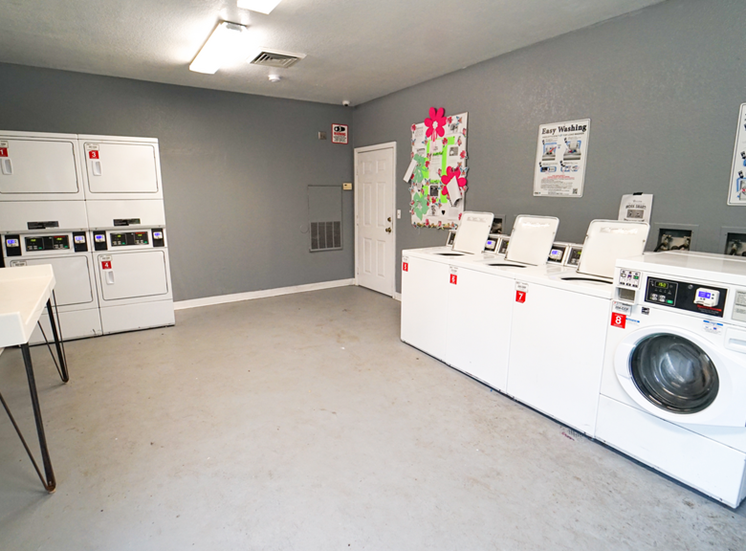 Resident laundry facility with washers, dryers, tiled flooring, and folding station