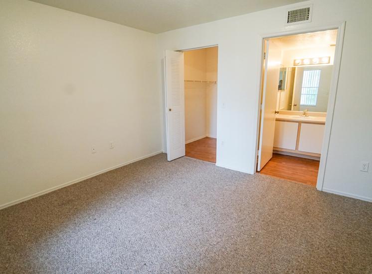 Bedroom with carpet flooring, walk-in closet, and en-suite bathroom