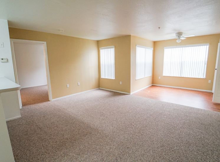 Living room with carpet flooring, dining room with hardwood style flooring, and large windows for natural lighting