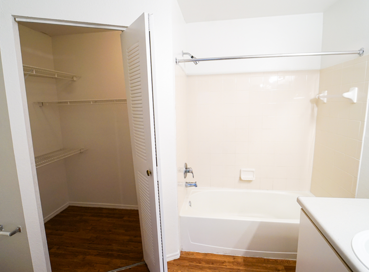 Bathroom with hardwood flooring, tiled shower, and walk-in closet