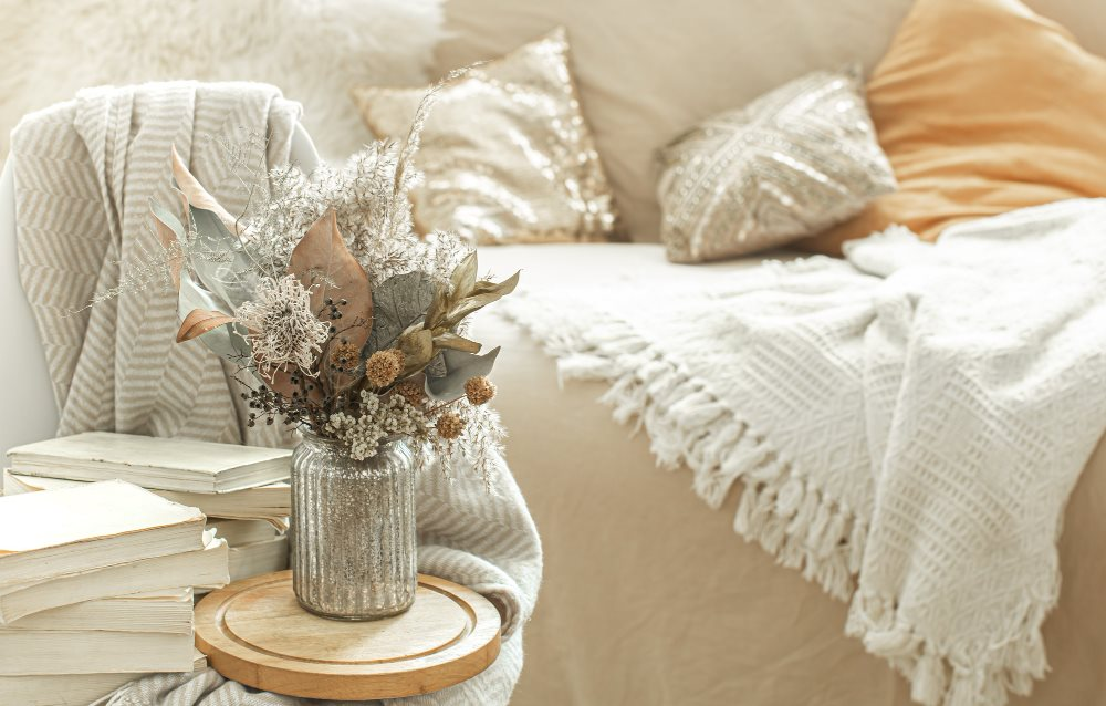 Ashbrooke Apartments Homepage Slider Image A Couch with a vase of flowers in front of it and some decorative books