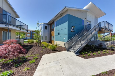 Apartment Exterior with Walking Path, Lavender Tree, Wood Chip Floor, Blue Apartment Exterior with Staircase